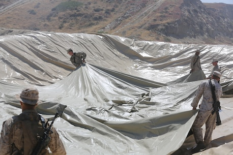 U.S. Marines with Bulk Fuel Company, 7th Engineer Support Battalion, 1st Marine Logistics Group, roll out a bag liner on Camp Pendleton, Calif., May 1, 2015. The bag liner is used as part of the Beach Unloading System used to house fuel which is pumped from a ship off shore. (U.S. Marine Corps Photo by Cpl. Rodion Zabolotniy, Combat Camera/Released)
