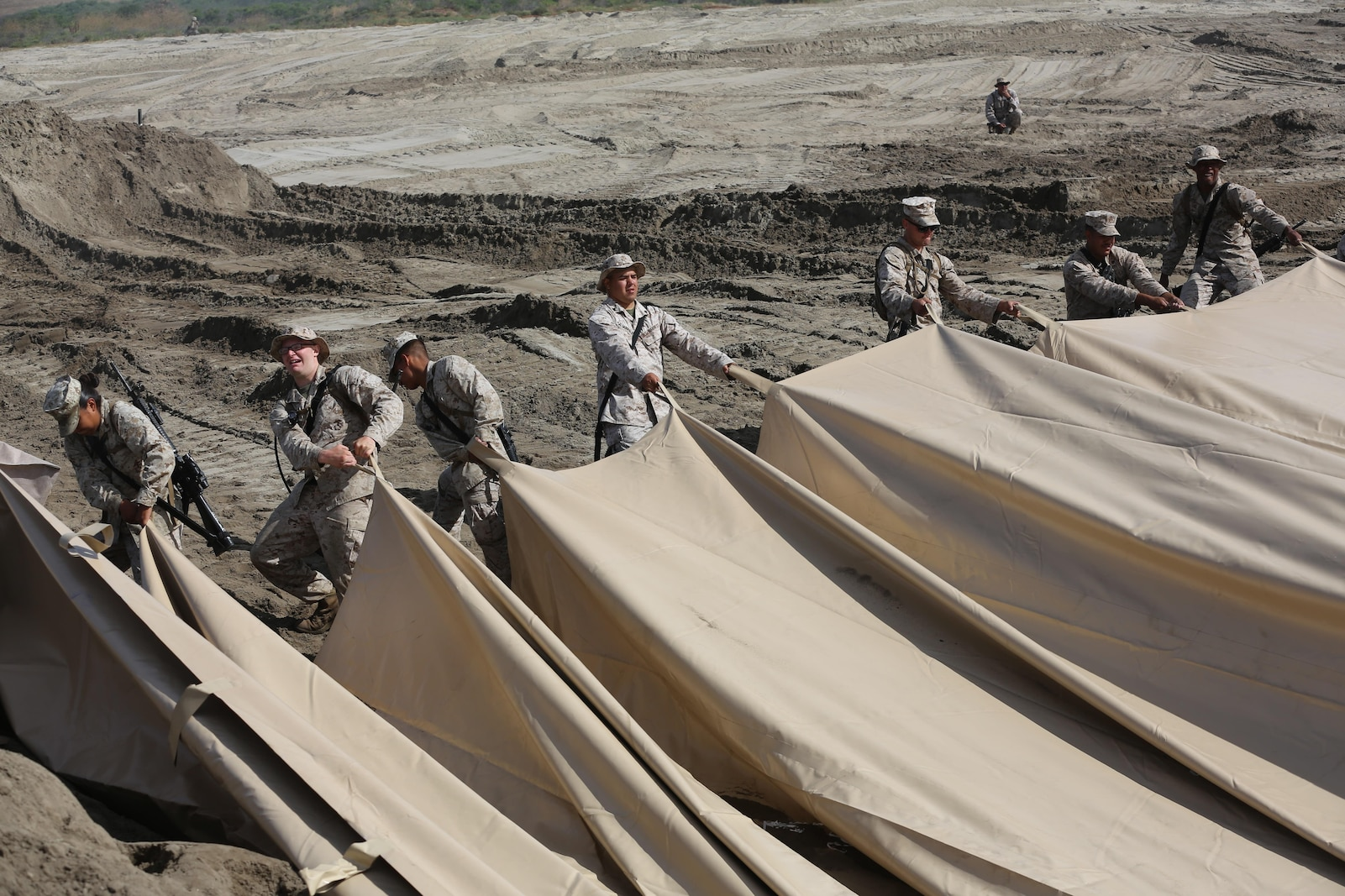 U.S. Marines with Bulk Fuel Company, 7th Engineer Support Battalion, 1st Marine Logistics Group, roll out a berm liner on Camp Pendleton, Calif., May 1, 2015. The berm liner is used as part of the Beach Unloading System used to house fuel, which is pumped from a ship off shore. (U.S. Marine Corps Photo by Cpl. Rodion Zabolotniy, Combat Camera/Released)