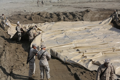 U.S. Marines with Bulk Fuel Company, 7th Engineer Support Battalion, 1st Marine Logistics Group, roll out a berm liner on Camp Pendleton Calif., May 1, 2015. The berm liner is used as part of the Beach Unloading System used to house fuel, which is pumped from a ship off shore. (U.S. Marine Corps Photo by Cpl. Rodion Zabolotniy, Combat Camera/Released)