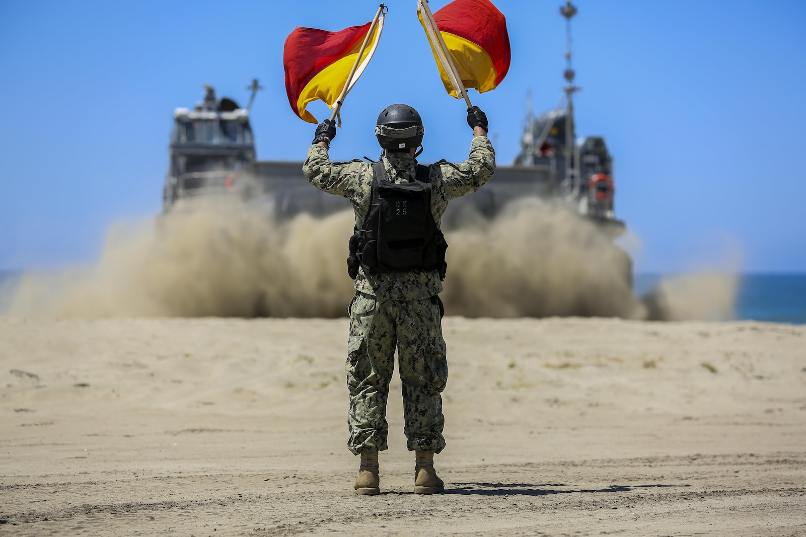 U.S. Navy Landing Craft Air Cushioned (LCAC) vehicle from Assault Craft Unit 5 is guided off of Red Beach as part of a training exercise alongside Bulk Fuel Company, 7th Engineer Support Battalion aboard Camp Pendleton, Calif., April 27, 2015. This exercise reinforces the Marine Corps role as an amphibious force in readiness by maintaining capabilities through realistic training.(U.S. Marine Corps photo by Lance Cpl. Lauren Falk/Released)
