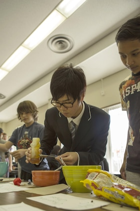 Students with Matthew C. Perry High School and Noda Gakuen High School make sacks during a visit to M.C. Perry aboard Marine Corps Air Station Iwakuni, Japan, April 24, 2015. The visit is part of the Noda Gakuen High School's Global International Course, thats main focus is to give students resources needed to improve language and communication skills, understand their roles in different societies and actively challenge themselves to try new things.