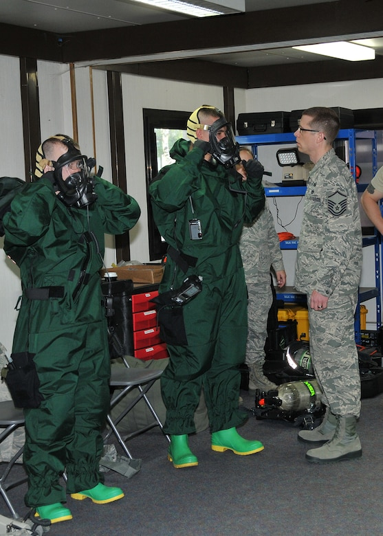 Master Sgt. Christopher McCrary, Emergency Management Flight non-commissioned officer in charge, Barnes Air National Guard Base, Westfield, Mass., inspects Airman 1st Class Neal Colburn and active-duty Staff Sgt. John Gaylord in their Personal Protection Level-B suits during an exercise May 6, 2015, Spangdahlem Air Base, Germany. The Guard and active-duty Airmen are training together on Active CBRNE (Chemical Biological Radiological Nuclear and High- Yield Explosives) Response to enhance their Hazmat Technician Certification. This is a required training that needs to be done by the guard and the active duty. Doing the training together allows them to increase their knowledge by sharing their experiences and use different types of equipment. (U.S. Air National Guard photo by Tech. Sgt. Melanie J. Casineau/Released)