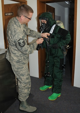 Master Sgt. Christopher McCrary, 104th Emergency Management Flight non-commissioned officer in charge, Barnes Air National Guard Base, Westfield, Mass., inspects the Personal Protection Level B suit on Tech. Sgt. Nicole Locke, 104th Emergency Management Flight, during an exercise May 6, 2015, Spangdahlem Air Base, Germany. McCrary and Locke are training on Active CBRNE (Chemical Biological Radiological Nuclear and High- Yield Explosives) Response with the active-duty members to enhance their Hazmat Technician Certification. This is a required training that needs to be done yearly by the guard and the active duty. Doing the training together allows them to increase their knowledge by sharing their experiences and use different types of equipment. (U.S. Air National Guard photo by 2nd Lt. Bonnie Harper /Released)