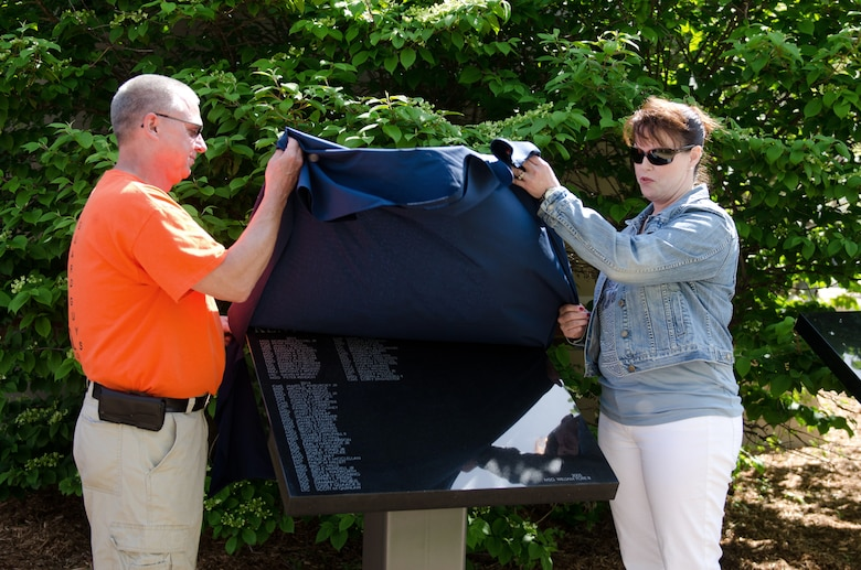 Retired Senior Master Sgt. Gary Dunlap and Retired Chief Master Sgt. Lori F. Zinsmeister unveil a plaque bearing the names of more than 50 Airmen who retired from the 123rd Airlift Wing last year during a ceremony at the Kentucky Air National Guard Base in Louisville, Ky., April 18, 2015.  The annual unveiling celebrates Airmen who served for 20 or more years. (U.S. Air National Guard photo by Senior Airman Joshua Horton)