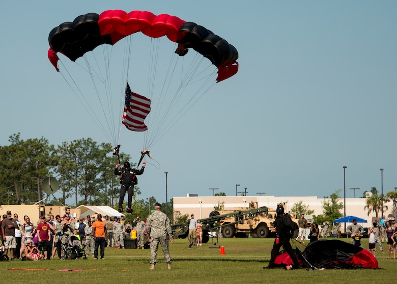 Members of the U. S. Army Special Operations Command's Black Daggers Parachute Demonstration Team drop onto Eglin Air Force Base during the 7th Special Forces Group (Airborne) Red Empire Week Community Day May 5.  A Duke Field C-145 flew to serve as the team's free-fall jump platform.  (U.S. Air Force photo/Tech. Sgt. Jasmin Taylor)