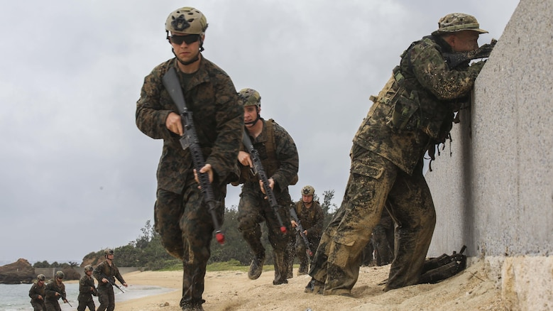 Japanese Ground Self-Defense Force soldiers post security as U.S. Marines advance on the beach during the Japanese Observer Exchange Program April 28, 2015 at Kin Blue. JOEP is a III Marine Expeditionary Force, 31st Marine Expeditionary Unit and JGSDF coordinated program designed to increase regional security, maintain unit readiness and enhance overall cooperation. This is the fourth iteration of JOEP for the 31st MEU after the initial partnership in September 2012. The Marines are with Battalion Landing Team 2nd Battalion, 4th Marines, 31st MEU. (U.S. Marine Corps photo by Cpl. Ryan C. Mains/Released)