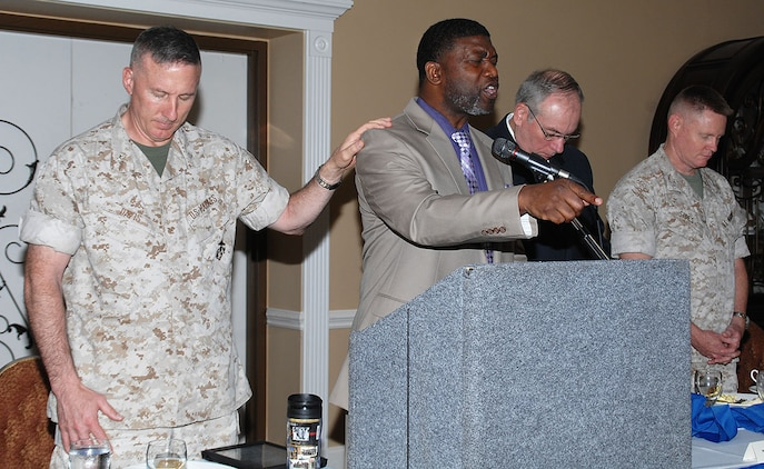 Guest speaker Kurt Bland, (center) deputy director, Communications and Information Systems Division, Marine Corps Logistics Base Albany, prays during the annual National Day of Prayer Breakfast at the Town and Country Restaurant's Grand Ballroom, May 7. Col. Don J. Davis, (left) commanding officer, MCLB Albany; Michael T. Madden, executive deputy, and Col. Charles L. Sides, chief of staff, both with Marine Corps Logistics Command, attended the annual event, which also marks the 64th annual National Day of Prayer.