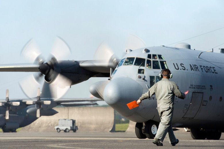 A crew chief with the 374th Aircraft Maintenance Squadron guides a C-130 Hercules to the taxiway at Yokota Air Base, Japan, May 5, 2015. Members of Yokota provided humanitarian airlift and relief operations to support the U.S. Agency of International Development and the government of Nepal in response to the 7.8 magnitude earthquake that devastated the country April 25, 2015. (U.S. Air Force photo/Staff Sgt. Cody H. Ramirez)