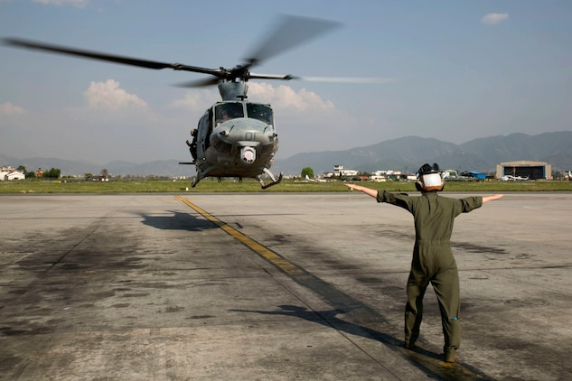 Cpl. Mackenzie Higgins guides a UH-1Y Huey for takeoff at the Tribhuvan International Airport in Kathmandu, Nepal, May 5. Marines with Marine Light Attack Helicopter Squadron 469 and Marine Medium Tilt Rotor Squadron 262 carried supplies in a UH-1Y Huey and MV-22 Ospreys to Charikot, Nepal. The supplies will provide Nepalese people with shelter after a 7.8 magnitude earthquake struck central Nepal, April 25, causing fatalities, injuries and significant damage. The government of Nepal declared a state of emergency and requested international assistance. The U.S. military, at the direction of the U.S. Agency for International Development, will continue to support Nepal as needed. HMLA-469 and VMM-262 are attached to Marine Aircraft Group 36, 1st Marine Aircraft Wing, III Marine Expeditionary Force. Higgins is a UH-1Y crew chief with HMLA-469 from Pala Way, California.