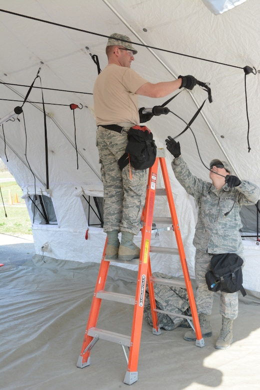Airmen from the 115th Fighter Wing set up inside a medical tent during a two-day Chemical, Biological, Radiological, Nuclear and Explosives Enhanced Response Force Package exercise at Volk Field Air National Guard Base, Wis., May 1-2. The exercise allowed service members to prepare for the first ever CERFP one-day inspection, scheduled to be held in June 2015. (U.S. Air National Guard photo by Senior Airman Andrea F. Rhode)