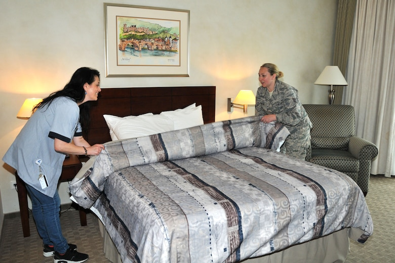 Staff Sgt. Adrianne Johnson, 104th Services Flight, Barnes Air National Guard Base, Westfield, Mass., finishes making a bed with Sophia Kourtidou, housekeeper, May 7, Air Force Inn, Kaiserslautern Military Community Center, Ramstein Air Base, Germany. This was part of Johnson's housekeeping training at the KMCC Air Force Inn May 5-7. She additionally trained on inspecting rooms, accounting, reservations, and supply, allowing her to sign off on requirements for her services position. (U.S. Air National Guard photo by Tech. Sgt. Melanie J. Casineau/ Released)