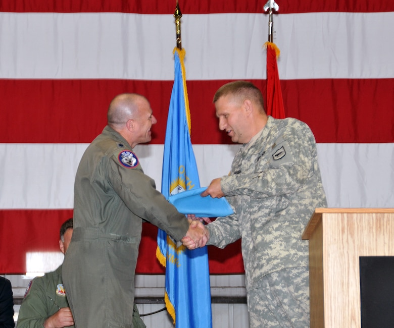 U.S. Air Force Lt. Col. Todd M. Sheridan, 175th Fighter Squadron commander and detachment commander, accepted a South Dakota state flag from Maj. Gen. Tim Reisch, the adjutant general for the South Dakota National Guard, during a mobilization ceremony held at Joe Foss Field, S.D., May 3, 2015. The South Dakota Air National Guard's 114th Fighter Wing is slated to deploy to South Korea and it is customary that the adjutant general present a state flag to the detachment commander in charge, which he will display at their deployed location. (U.S. Air National Guard photo by Tech. Sgt. Christopher Stewart)