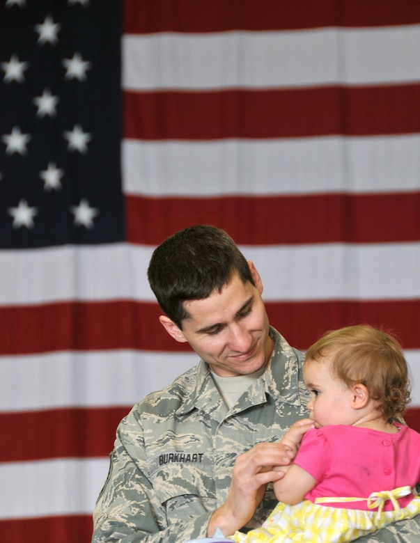U.S. Air Force Tech. Sgt. Derrick Burkhart, 114th Maintenance Squadron munitions controller, holds his daughter Arianna, before the start of a mobilization ceremony at Joe Foss Field, S.D., May 3, 2015. Burkhart is part of the almost 250 members of the South Dakota Air National Guard's 114th Fighter Wing preparing to depart for a four month deployment to South Korea where they will support the United States' continual commitment to stability and security in the region. (Photo by Tech. Sgt. Christopher Stewart)