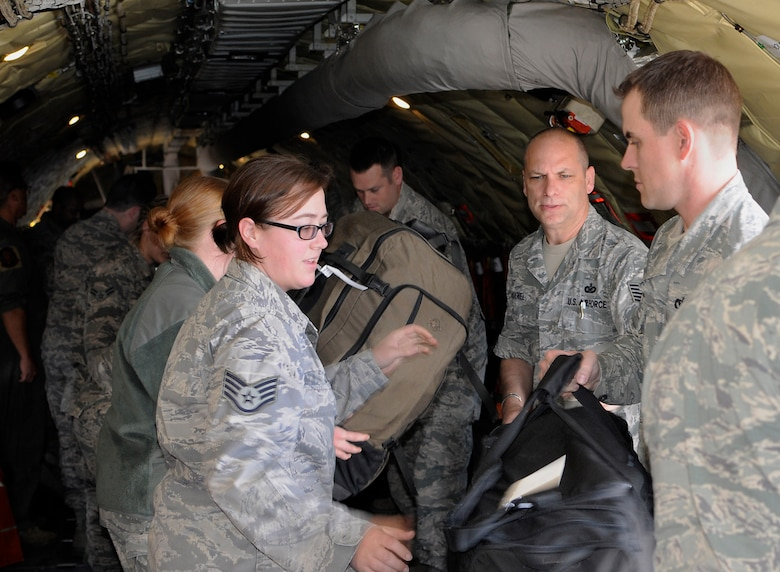 Members of the 142nd Fighter Wing Civil Engineer Squadron (CES) form a line to load baggage into a KC-135 Stratotanker at the Portland Air National Guard Base, Ore., May 5, 2015. The 142nd CES is taking part in a mission to Romania to rebuild an aging hospital as part of US European Command's Humanitarian Assistance Program. (U.S. Air National Guard photo by Staff Sgt. Brandon Boyd, 142nd Fighter Wing Public Affairs/Released)