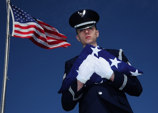 Senior Airman Travis Von Elling, 319th Air Base Wing Honor Guard ceremonial guardsman, poses with the flag May 5, 2015 on Grand Forks Air Force Base, N.D. Von Elling was selected as the Warrior of the Week for the first week of May 2015. (U.S. Air Force photo by Airman 1st Class Ryan Sparks/released)
