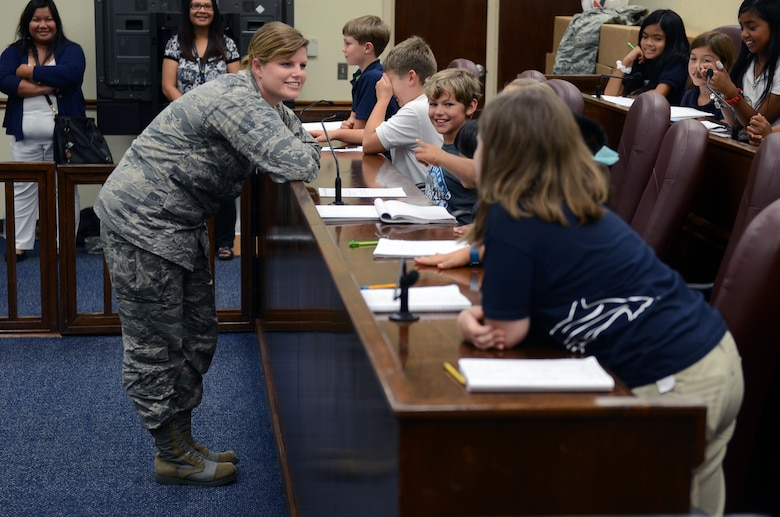 Capt. Natalie Cepak, 36th Wing officer in charge of civil law, discusses the mock trial's deliberation with Andersen Elementary School fourth graders in the base courtroom May 1, 2015, at Andersen Air Force Base, Guam. The 36th Wing Paralegal team acted out an Alice in Wonderland-themed mock trial for Law Day, May 1, to explain the importance of the Magna Carta. (U.S. Air Force photo by Airman 1st Class Alexa Ann Henderson/Released)