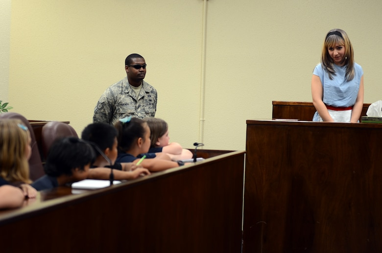 Airman 1st Class Alyssa Moreno, 36th Wing military justice paralegal, testifies to Andersen Elementary School fourth graders as Alice at the base courtroom May 1, 2015, at Andersen Air Force Base, Guam. The 36th Wing Paralegal team acted out an Alice in Wonderland-themed mock trial for Law Day to explain to students the importance of the Magna Carta. (U.S. Air Force photo by Airman 1st Class Alexa Ann Henderson/Released)