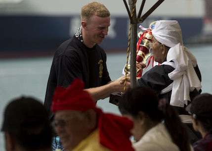 Lance Cpl. Kevin D. Jolly, left, a basic electrician with Facilities Engineering, Marine Corps Installations, Pacific-Marine Corps Base Camp Butler, Japan, accepts a trophy from Masaharu Minei, chief of the dragon boat organization, on behalf of the Single Marine Program dragon boat team May 5 during the 41st annual Naha City Dragon Boat Races, also known as Harii, at Tomari Port in Naha City, Okinawa. More than 60 teams competed in the races, making a total of approximately 2,300 participants. Three teams, consisting of 32 people per boat, competed against each other in every race. The SMP dragon boat team was made up of approximately 44 Marines and sailors. SMP was slated to participate in two races during the event, but winning their first race with a time of five minutes and 33 seconds, they earned a place to compete in a third race — for the championship. (U.S. Marine Corps photo by Lance Cpl. Brittany A. James/Released)