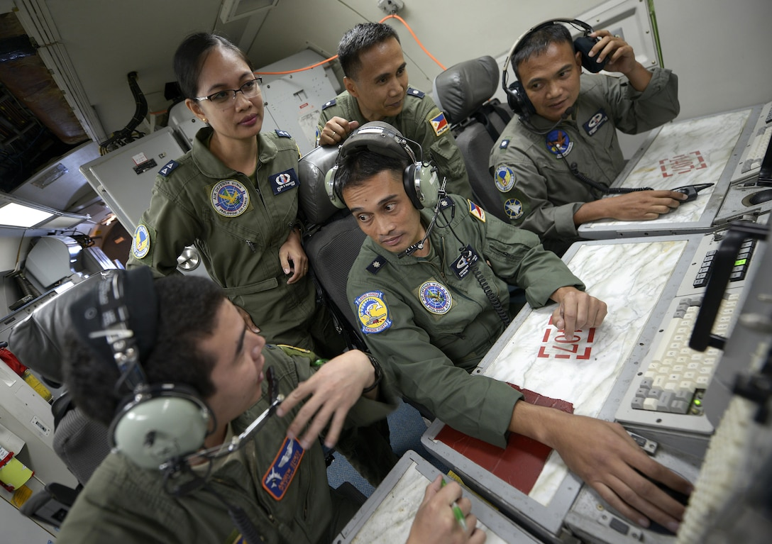 1st Lt. Andrew Stokes (left), a 961st Airborne Air Control Squadron (AACS) air weapons officer, speaks with Philippine Air Force Maj. Frederick Facia, the 581st Aircraft Control and Training Squadron commander, and other PAF air battle managers while onboard a 961st AACS E-3 Sentry AWACS during exercise Balikatan 2015 over the Philippines April 23, 2015. This exercise marks the first time in history that PAF air battle managers have controlled other aircraft while on board the AWACS. Since the exercise began, April 20, 2015, the 961st AACS has integrated 20 PAF weapons controllers during their missions in order to provide them with firsthand experience using the aircraft's systems. The 961st AACS is stationed at Kadena Air Base, Japan. (U.S. Air Force photo/Staff Sgt. Maeson L. Elleman)