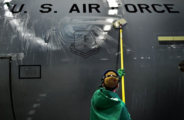 An Airman from the 86th Aircraft Maintenance Squadron washes the underside of a C-130J Super Hercules April 20, 2015, at Ramstein Air Base, Germany. Aircraft washing is a vital part of the flying mission, and if not washed regularly, aircraft begin to corrode and cause damage yielding it unsafe to operate. Safety procedures require all members participating in the washing to wear full-body protective gear. (U.S. Air Force photo/Staff Sgt. Sara Keller)