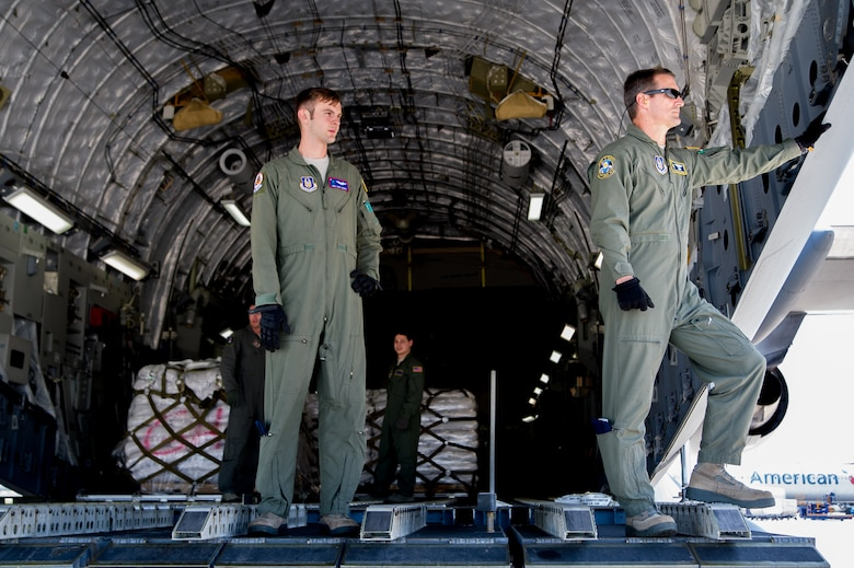 Master Sgt. Ken Hundemer, 317th Airlift Squadron loadmaster, and Tech Sgt. Cody Harris, 701st Airlift Squadron loadmaster, awaits the arrival of a cargo offload vehicle April 23, 2015 in Haiti during a four-day training mission to Key West Naval Air Station, Fla. The 315th Airlift Wing flew 20 sorties during the four-day deployment and airlifted more than 345,000 pounds of humanitarian cargo, which included 61 pallets of food and clothing and one school bus. Hundemer he also serves as the Denton Program director of operations in his civilian capacity. (U.S. Air Force Photo by Tech. Sgt. Shane Ellis)