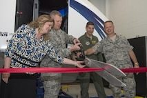 U.S. Air Force Col. Samuel Milam, Air Education and Training Command eputy director of intelligence operations and nuclear intelligence for flying training, (left), cuts the ribbon for AETC's first Spatial Disorientation Trainer beside Valerie Dahlem, from the Air Force Life Cycle Management Center, (far left), Col. Gregory Keeton, 80th Flying Training Wing commander, (right), and Col. Gregory DeWolf, 82nd Medical Group commander, (far right), at Sheppard Air Force Base May 7, 2015. The trainer simulates different air sicknesses that pilots may experience when flying. Instructors have the ability to walk student pilots through these experiences, teaching them how to combat the disorientation effectively. (U.S. Air Force photo by Senior Airman Kyle Gese/Released)