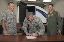 U.S. Air Force Col. Samuel Milam, Air Education and Training Command deputy director of intelligence operations and nuclear intelligence for flying training, (middle), signs the formal acceptance of AETC's first Spatial Disorientation Trainer beside Col. Gregory DeWolf, 82nd Medical Group commander, (left), and Col. Gregory Keeton, 80th Flying Training Wing commander, at Sheppard Air Force Base May 7, 2015. The trainer is intended to teach pilots how to correctly identify different types of air sickness they may encounter during flight. (U.S. Air Force photo by Senior Airman Kyle Gese/Released)