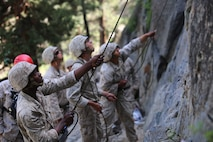Marines with the Ground Combat Element Integrated Task Force belay their partners during the 40-foot cliff face climbing event of a during a Marine Corps Operational Test and Evaluation Activity assessment aboard Marine Corps Mountain Warfare Training Center Bridgeport, California, May 5, 2015. From October 2014 to July 2015, the GCEITF will conduct individual and collective level skills training in designated ground combat arms occupational specialties in order to facilitate the standards-based assessment of the physical performance of Marines in a simulated operating environment performing specific ground combat arms tasks. (U.S. Marine Corps photo by Cpl. Paul S. Martinez/Released)