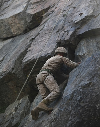 Cpl. Jordan Yearsley, combat engineer, Engineer Platoon, Headquarters and Service Company, Ground Combat Element Integrated Task Force, climbs a 40-foot cliff face during a pilot Marine Corps Operational Test and Evaluation Activity assessment aboard Marine Corps Mountain Warfare Training Center Bridgeport, California, May 5, 2015. From October 2014 to July 2015, the GCEITF will conduct individual and collective level skills training in designated ground combat arms occupational specialties in order to facilitate the standards-based assessment of the physical performance of Marines in a simulated operating environment performing specific ground combat arms tasks. (U.S. Marine Corps photo by Cpl. Paul S. Martinez/Released)
