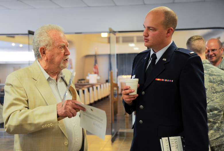 U.S. Air Force Pawel Linchter, Holocaust survivor, talks with 2nd  Lt Charles Hulsizer, 355th Force Support Squadron, following the Holocaust Day of Remembrance at Davis-Monthan Air Force Base, Ariz., May 7, 2015. Each of the Holocaust survivors was presented with a memento that created from the aircraft aluminum, shaped like a butterfly to represent freedom and hope. (U.S. Air Force photo by Staff Sgt. Angela Ruiz/Released)
