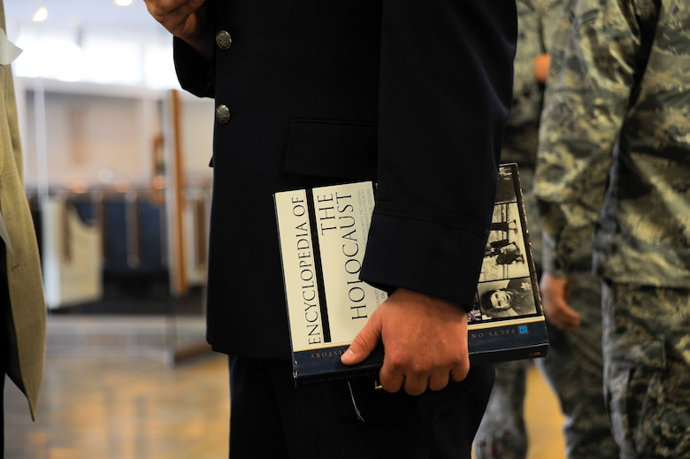 "U.S. Air Force 2nd Lt Charles Hulsizer, 355th Force Support Squadron,  holds the ""Encyclopedia of the Holocaust"" during the Holocaust Day of Remembrance at Davis-Monthan Air Force Base, Ariz., May 7, 2015. Six holocaust survivors spoke to over 90 people about their personal experiences and survival during the Holocaust.  (U.S. Air Force photo by Staff Sgt. Angela Ruiz/Released)"