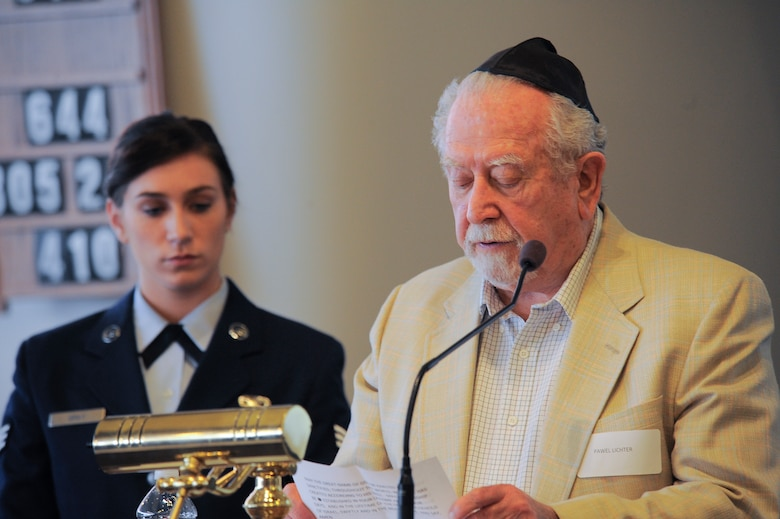 "Pawel Linchter, Holocaust survivor, recites the prayer ""Mourner's Kaddish"" in Hebrew while Senior Airman Delanie Gray, 355th Comptroller Squadron, listens during the Holocaust Day of Remembrance at Davis-Monthan Air Force Base, Ariz., May 7, 2015. The ""Mourner's Kaddish"" is a prayer of remembrance, which Gray translated in English for the audience. (U.S. Air Force photo by Staff Sgt. Angela Ruiz/Released)"