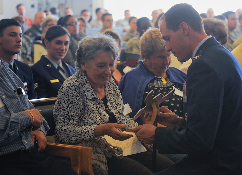 Lilly Brull, Holocaust survivor, is presented with a memento of appreciation from Col. James Meger, 355th Fighter Wing commander, during the Holocaust Day of Remembrance at Davis-Monthan Air Force Base, Ariz., May 7, 2015. The memento was created from  aircraft aluminum and shaped like a butterfly to represent freedom and hope.