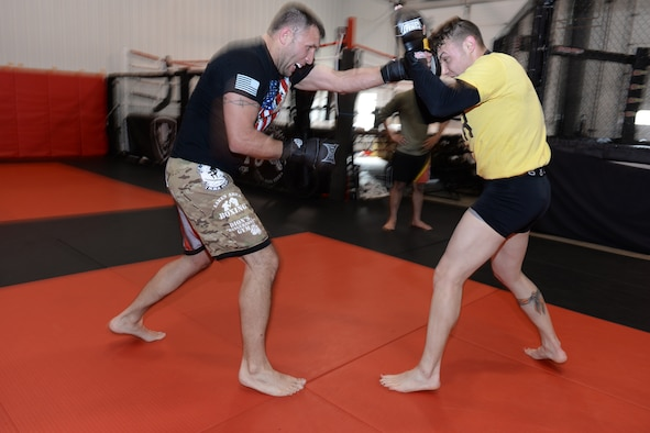 119th Security Forces members from left to right Tech. Sgt. Gemenie Strehlow and Senior Airman Michael Bullen exchange punches as they spar while training at a Fargo, North Dakota, gym May 8, 2015. The security forces Airmen are training at the gym to enhance their fitness and skills to be better prepared in their career field for potential threats on duty. Bullen is scheduled for a competitive mixed martial arts match May 16 in Detroit Lakes, Minnesota. (U.S. Air National Guard photo by Senior Master Sgt. David H. Lipp/Released)
