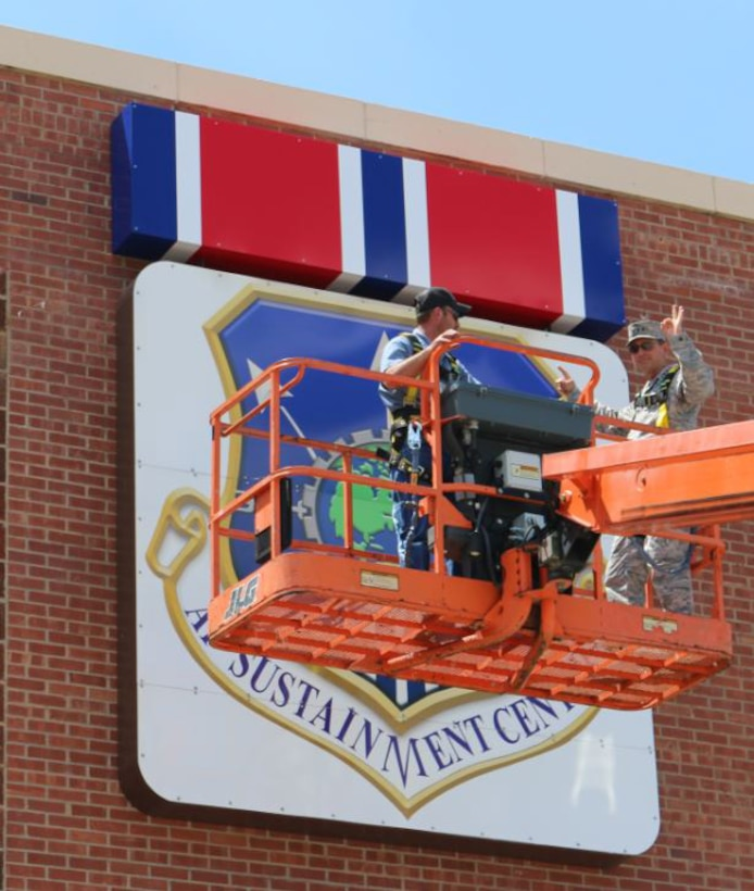 Air Force Sustainment Center Commander Lt. Gen. Bruce Litchfield gives his OK for the newly-installed Air Force Organizational Excellence ribbon on the front of Bldg. 3001. (Air Force photo by James Milton/Released)