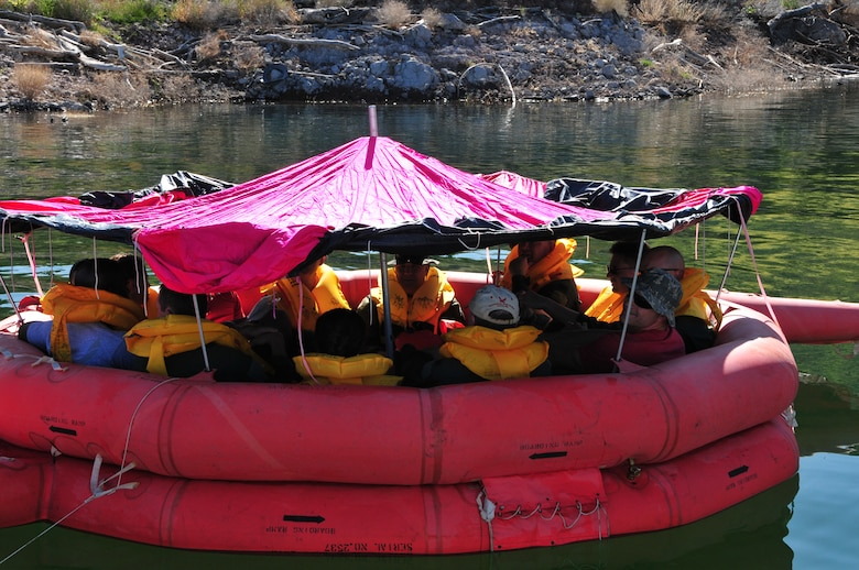 Airmen from the 161st Air Refueling Wing float in their 20 man life raft after rolling the sides of the canopy up for ventilation during water survival training at Lake Pleasant, Peoria, Ariz., May 3, 2015. Water survival training encompasses equipment familiarization and processes in the event of an emergency over-water ditching scenario.    (U.S. Air National Guard photo by Master Sgt. Kelly M. Deitloff)