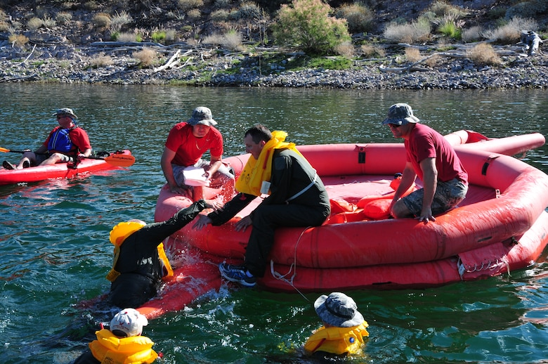 Senior Airman Michael Hastings, 161st  Air Refueling Wing boom operator, assists Col. Chris Triebel, 161st Air Refueling Wing vice commander, onto a 20 man life raft during water survival training May 3, 2015, at Lake Pleasant, Peoria, Ariz. Water survival training encompasses equipment familiarization and processes in the event of an emergency over-water ditching scenario.    (U.S. Air National Guard photo by Master Sgt. Kelly M. Deitloff)