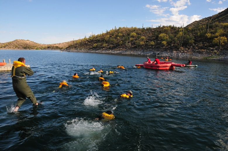 Airmen from the 161st Air Refueling Wing jump into Waddell Cove to simulate exiting an aircraft that has landed in the water during water survival training May 3, 2015, at Lake Pleasant, Peoria, Ariz. Water survival training encompasses equipment familiarization and processes in the event of an emergency over-water ditching scenario.    (U.S. Air National Guard photo by Master Sgt. Kelly M. Deitloff)