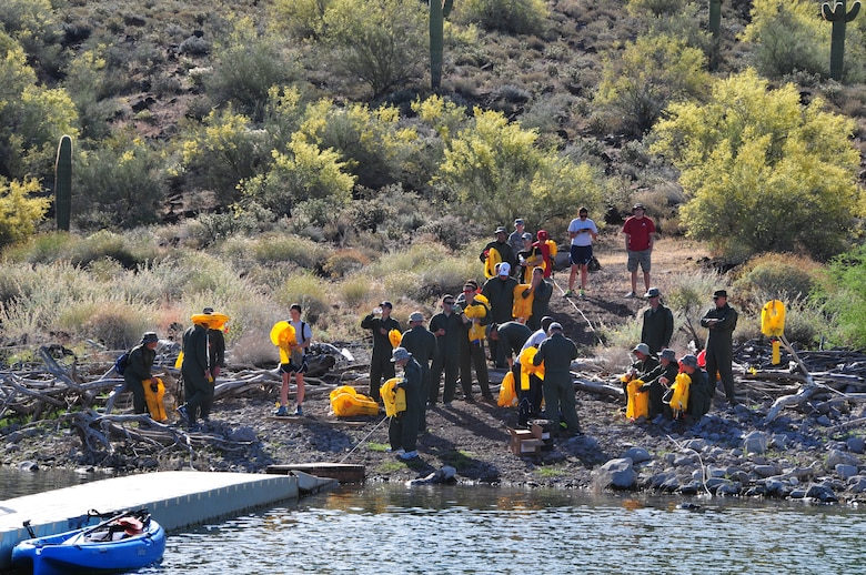 Airmen from the 161st Air Refueling Wing don their adult/child life preservers for water survival training at Lake Pleasant in Peoria, Ariz., May 3, 2015.  Water survival training encompasses equipment familiarization and processes in the event of an emergency over-water ditching scenario.    (U.S. Air National Guard photo by Master Sgt. Kelly M. Deitloff)