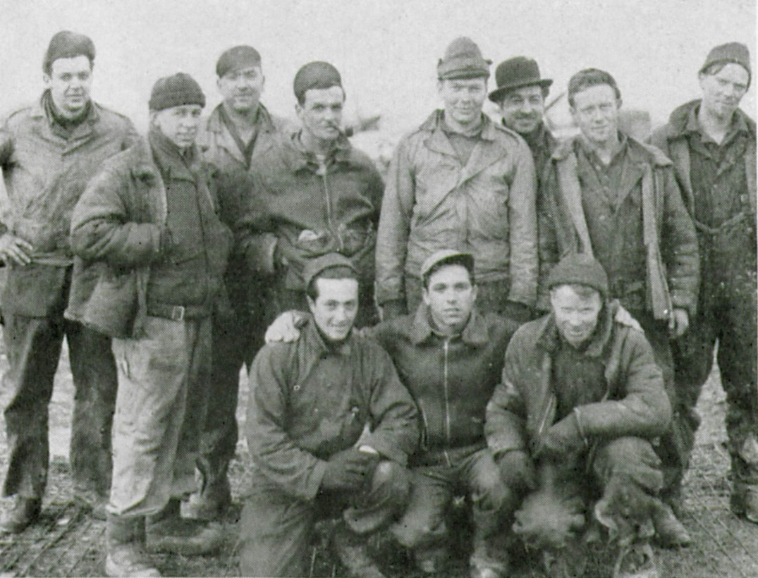 Enlisted men of the 405th Fighter Squadron who kept their Thunderbolts going in all kinds of conditions assemble for a flightline picture at a rugged airfield during some miserable winter weather.  Shown are their final wartime ranks.  Standing from left to right are S/Sgt John S. Piotrowski, Sgt. Donald E. Wright, S/Sgt Conrad M. Shelley, Sgt. Paul S. Kikta, T/Sgt William A. Morrison, S/Sgt Joseph L. Guarin, S/Sgt Francis T. Parker, Sgt. John J. Desmond.  Kneeling left to right are Sgt. Nicholas T. Mistretta, Cpl. Anthony J. Tenore and Sgt. Pearle S. Johnson. (The Story of the 371st Fighter Group in the E.T.O.)