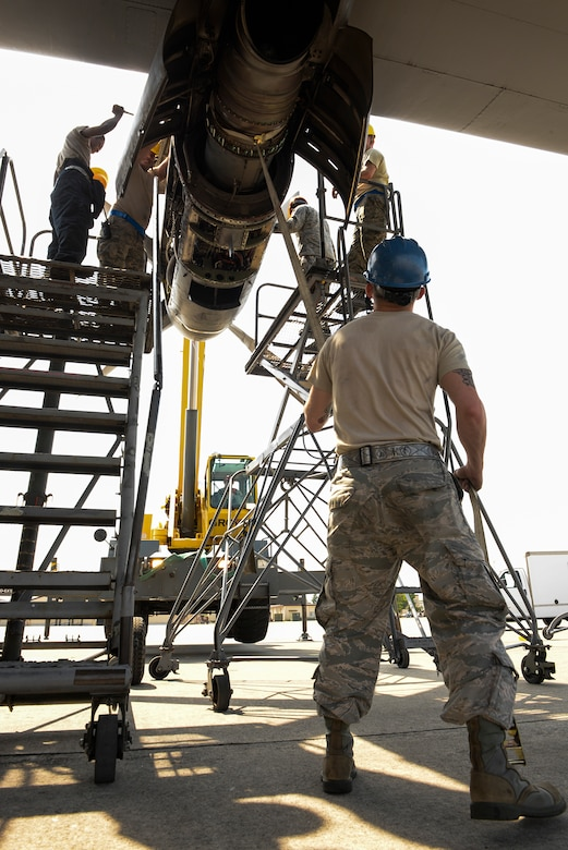 Staff Sgt. Dwayne Trett, aerospace propulsion craftsman with the 374th Maintenance Squadron, holds a strap to steady the engine of a C-130 Hercules, April 29, 2015 at Yokota Air Base, Japan. The process of removing the engine for repair took about 45 minutes of care and precision. (U.S. Air Force photo by Airman 1st Class Elizabeth Baker/Released)