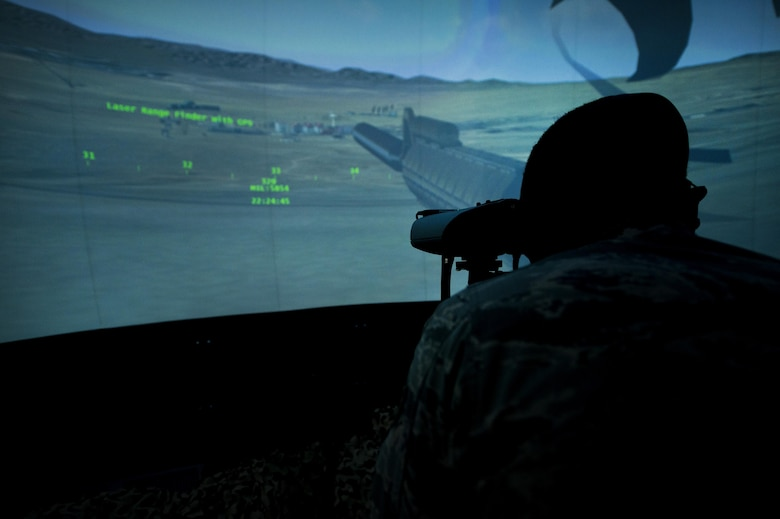 A tactical air control party Airman with the 14th Air Support Operations Squadron, surveys the landscape through a laser rangefinder inside the 6th Combat Training Squadron's joint terminal attack controller virtual training facility at Nellis Air Force Base, Nev., April 29, 2015. Since 2013, the 6th CTS has graduated more than 500 TACP Airmen from their JTAC Qualification Course which provides them with the experience and expertise required to call for live fire. (U.S. Air Force photo/Senior Airman Joshua Kleinholz)