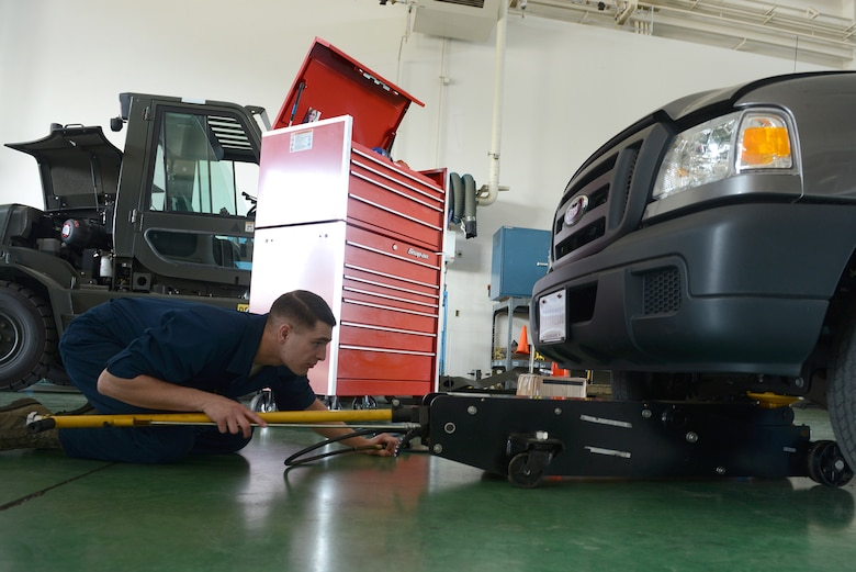 Senior Airman Brandon Higginbotham, a 374th Logistics Readiness Squadron vehicle maintenance journeyman, positions a jack under a government vehicle at Yokota Air Base, Japan, April 28, 2015. The truck was brought into the vehicle maintenance shop to assess the front brakes. (U.S. Air Force photo/Airman 1st Class David C. Danford)