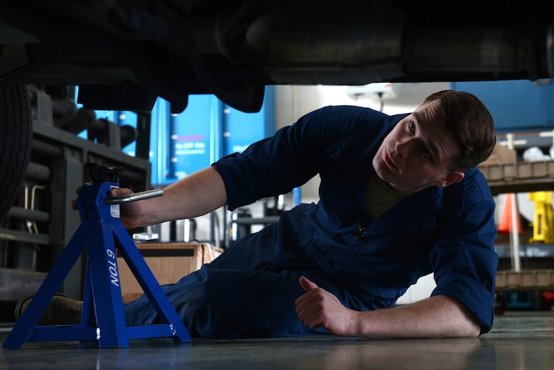 Senior Airman Brandon Higginbotham, a 374th Logistics Readiness Squadron vehicle maintenance journeyman, places jack stands under a government vehicle at Yokota Air Base, Japan, April 28, 2015. Stands are placed to ensure the safety of the mechanics working on vehicles. (U.S. Air Force photo/Airman 1st Class David C. Danford)