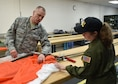 Master Sgt. Don McCormick, an aircrew life equipment craftsman with the 910th Airlift Wing, shows 12-year-old Celina Dennis of Poland, Ohio, how he inspects parachutes for defects here, May 6, 2015. Dennis was selected as the 910th Airlift Wing's 61st Pilot for a Day, being sworn in as an honorary 2nd Lt. and treated to a day of military-themed activities here. Pilots for a Day are local children with chronic or life-threatening illnesses selected by Akron Children's Hospital Boardman campus. (U.S. Air Force photo/Eric M. White)