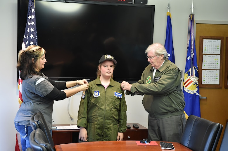 Carri Pullium (left) mother of twelve-year-old Celina Dennis (center), and Dale Pullium, Celina's grandfather, pin 2nd Lt. rank on her flight suit after she was sworn in as an honorary 2nd Lt. here, May 6, 2015. Dennis was selected as the 910th Airlift Wing's 61st Pilot for a Day and treated to a day of military-themed activities here. Pilots for a Day are local children with chronic or life-threatening illnesses selected by Akron Children's Hospital Boardman campus. (U.S. Air Force photo/Eric M. White)
