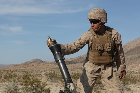 PFC Michael Ainsworth, a mortarman with Weapons Company, 3rd Battalion, 5th Marine Regiment, prepares to drop a mortar round during a combined-arms raid at Army National Training Center Fort Irwin, April 11, 2015. The raid was conducted by 1st Light Armored Reconnaissance Battalion as part of exercise Desert Scimitar 2015.