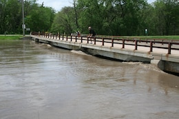 High water along Salt Creek in Lincoln, Nebraska nears the surface of a pedestrian bridge. Heavy rainfall on May 6, set record and near-record stages across the Salt Creek Basin.
