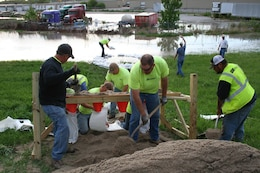 Crews fill sandbags and construct a ring of sand bags around a boil that formed along the Salt Creek Levee across from the Waste Water Treatment Plant in Lincoln, Nebraska, on May 7, 2015.