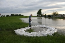 A representative from the Lower Papio South Natural Resources District places a sandbag on a ring of sandbags around a boil discovered along Salt Creek in Lincoln, Nebraska, across the creek from the Waste Water Treatment Plant